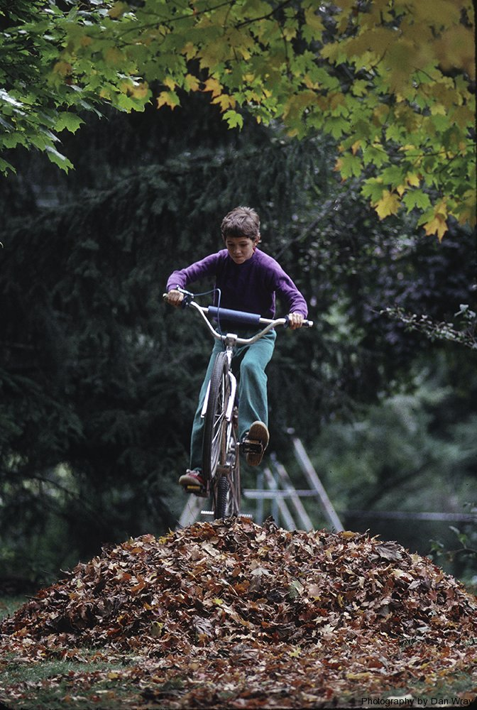 Elevin year old boy doing bike jump over Autumn leaves.