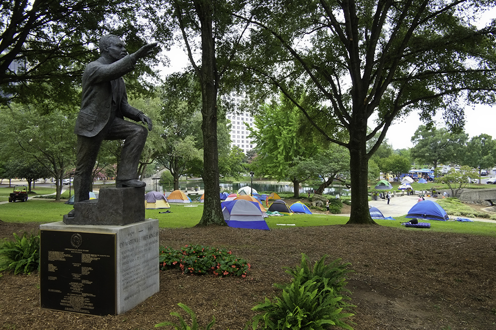 Protestors representing the Coalition to Occupy Wall Street South set up camp in Marshall Park in Charlotte, North Carolina during the Democratic National Convention, 2012. A statue of Martin Luther King, Jr. is featured in this park just above where protestors are camping.