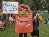 "Protestors representing the Coalition to Occupy Wall Street South set up camp in Marshall Park in Charlotte, North Carolina during the Democratic National Convention, 2012. This protestor showed up in a creative costume with the sign ""occupy my gas tank"" and a label ""can Obama."""