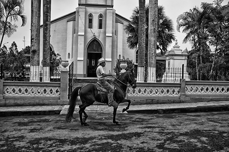 The Roman Catholic Church in the center of Atenas, Costa Rica, with a horseman (gaucho) riding past.
