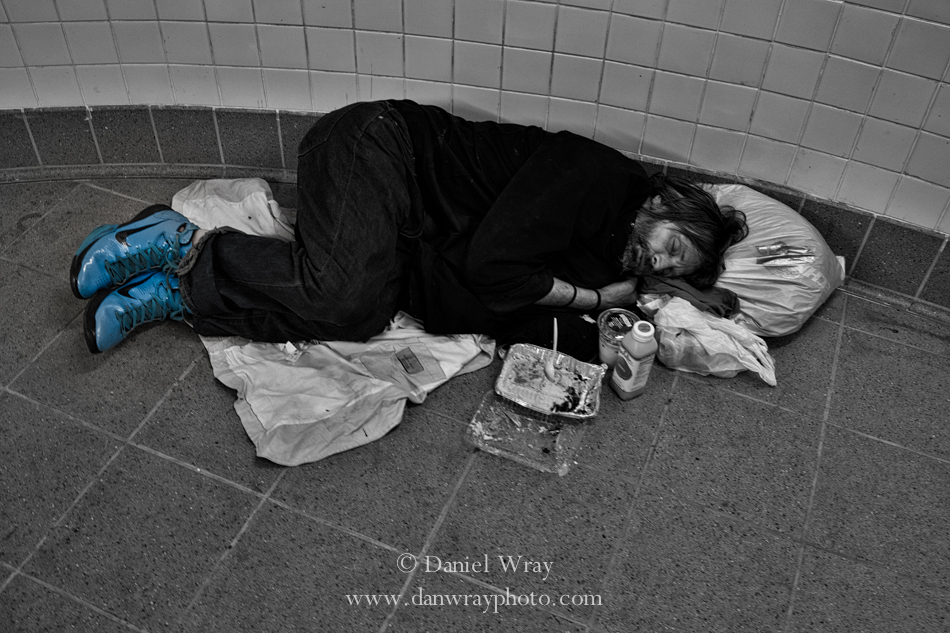 Man sleeping in subway hall.