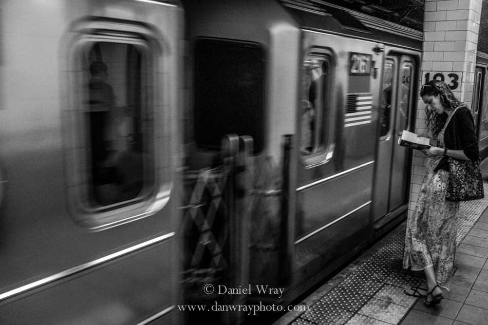 Woan Waiting and reading as the subway passes, Manhattan, New York.