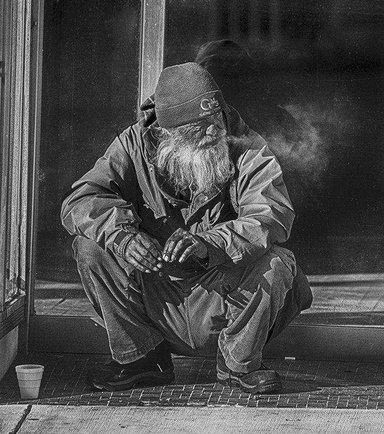 Man resting on the street with coffee and cigarette.
