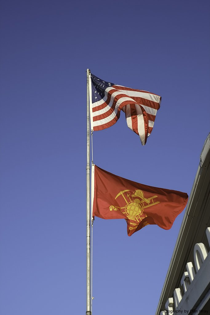 American flag and fireman\'s flag outside fire station in Mount Gilead, North Carolina.