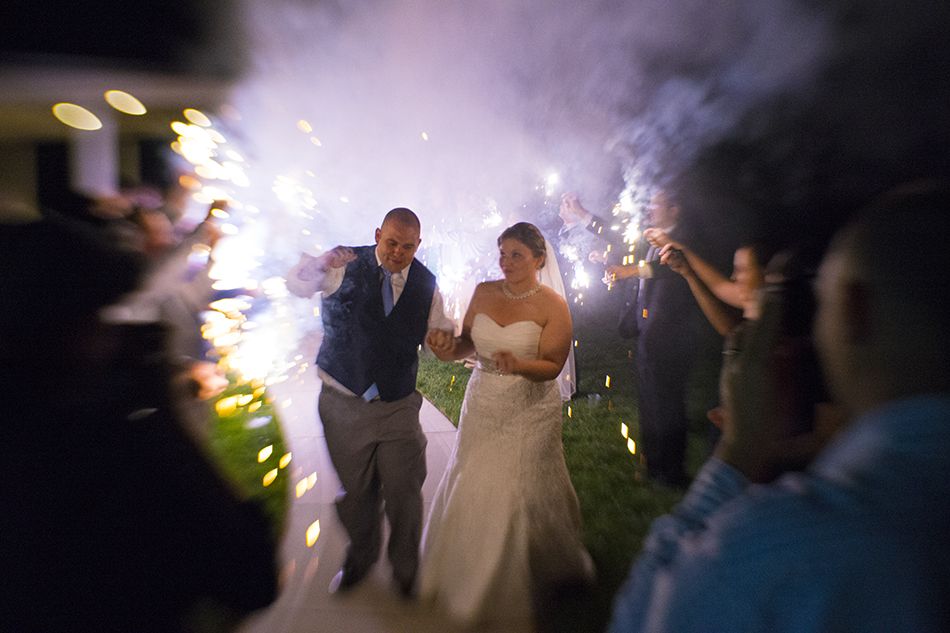 Bride and Groom passing through friends with sparklers as they leave the reception following the wedding.