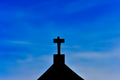 Silhouette of cross against fair weather sky.