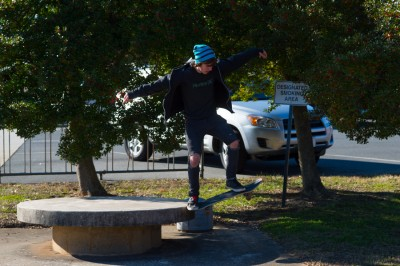 Teenage boy doing a skateboard jump off a bench in Albemarle, North Carolina.