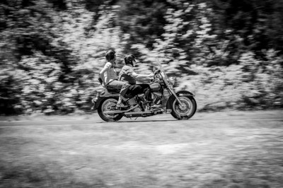 Couple speeding past on a Harley on a country road.