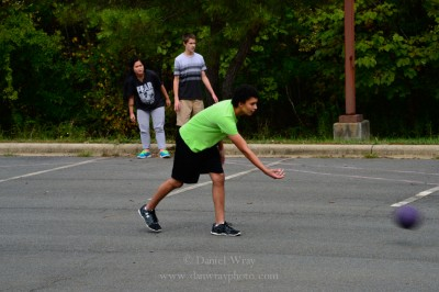 High school students playing kickball in a parking lot.