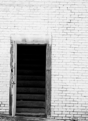 Door to darkened stairs.
