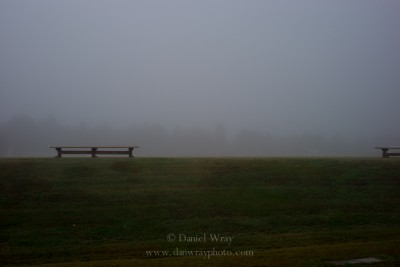 empty benches on a foggy morning at an athletic field.