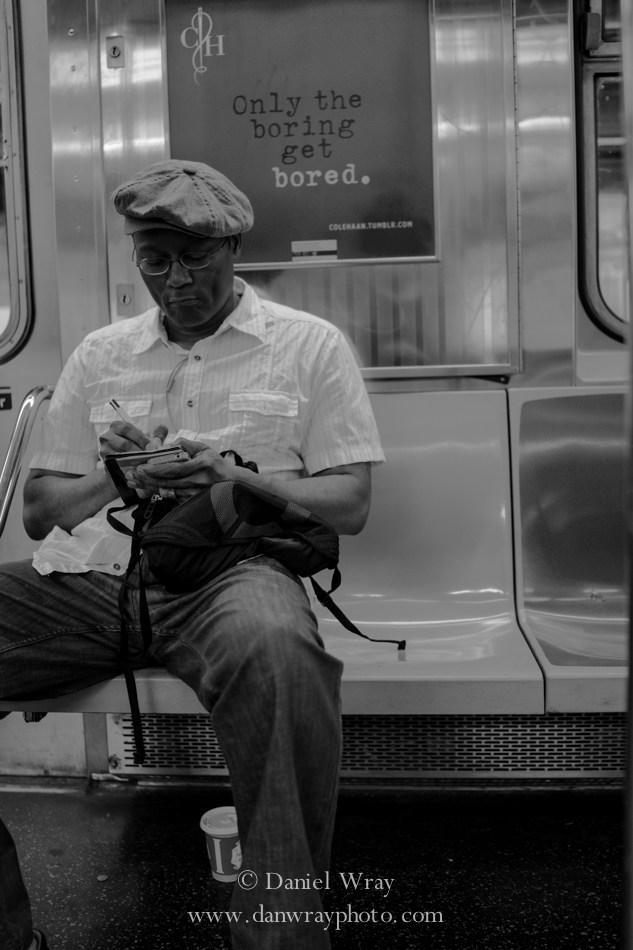 Man drawing as he rides the  A subway, Manhattan, New York.