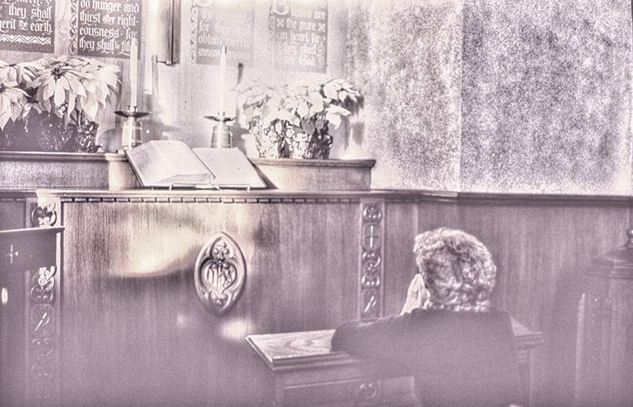Woman on her knees alone in prayer in a church. (MR)